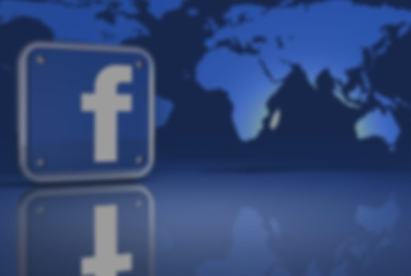 blurry facebook icon next to blue world map