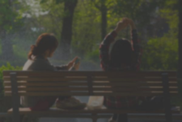 blurred image of people stretching and using phones on park bench